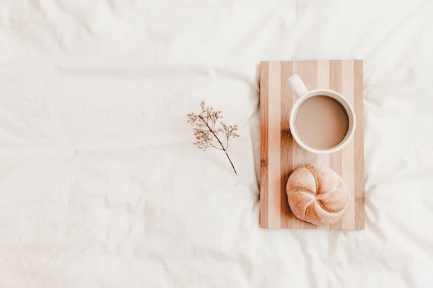 Boisson chaude et chignon sur planche à découper sur un drap blanc Photo gratuit