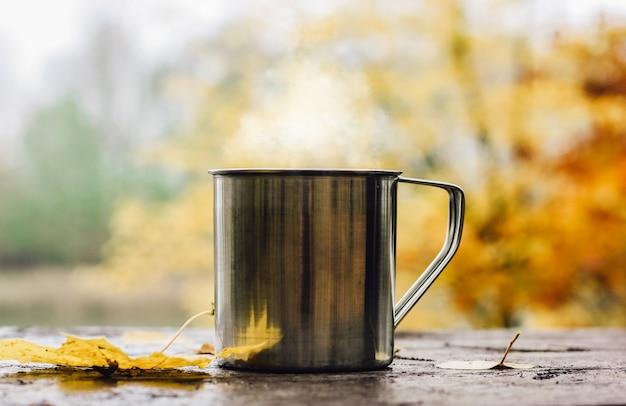 Boisson chaude dans la tasse en acier sur la table en bois. Photo Premium