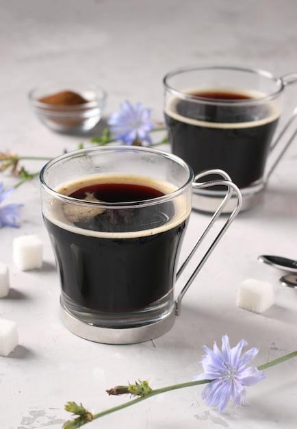 Boisson à La Chicorée Dans Deux Tasses En Verre, Avec Concentré Et Fleurs Sur Gris Photo Premium
