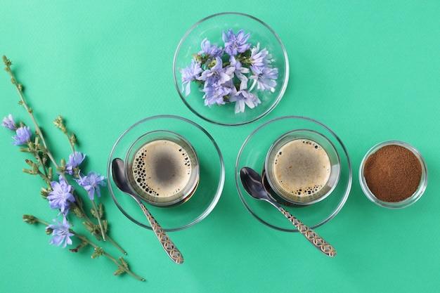 Boisson à La Chicorée Dans Deux Tasses En Verre, Avec Concentré Et Fleurs Sur Vert Photo Premium