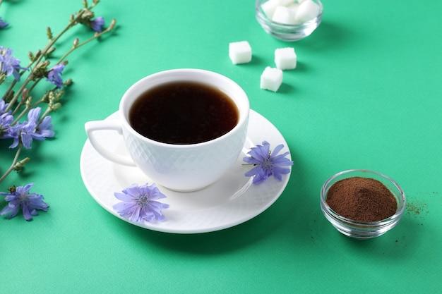 Boisson De Chicorée En Tasse Blanche, Avec Concentré Et Fleurs Sur Table Verte. Boisson Aux Herbes Saine, Substitut De Café, Gros Plan Photo Premium