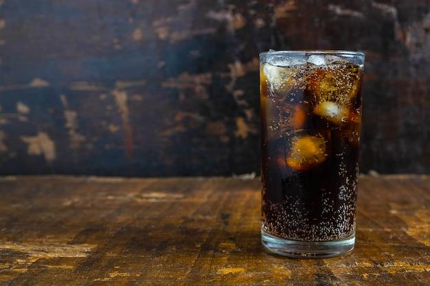 Boisson de cola, boissons gazeuses noires dans un verre sur la table Photo Premium