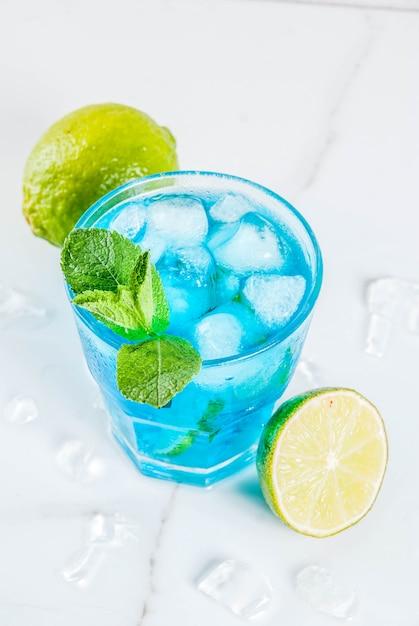 Boisson d'été colorée, boisson alcoolisée cocktail au lagon bleu glacé au citron vert et menthe Photo Premium