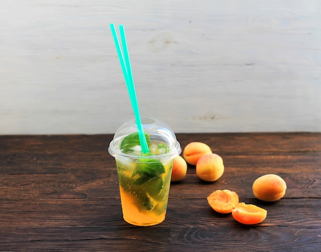 Boisson d'été limonade à l'orange et à la menthe dans le gobelet en plastique sur un fond sombre. Photo Premium