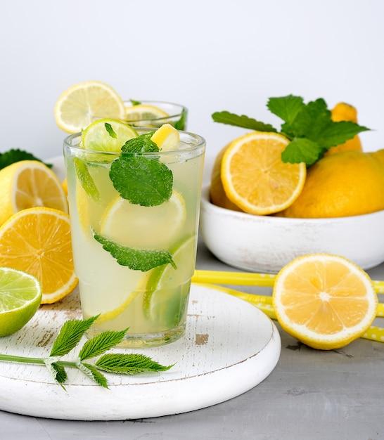 Boisson d'été limonade rafraîchissante avec citrons, feuilles de menthe, citron vert dans un verre Photo Premium