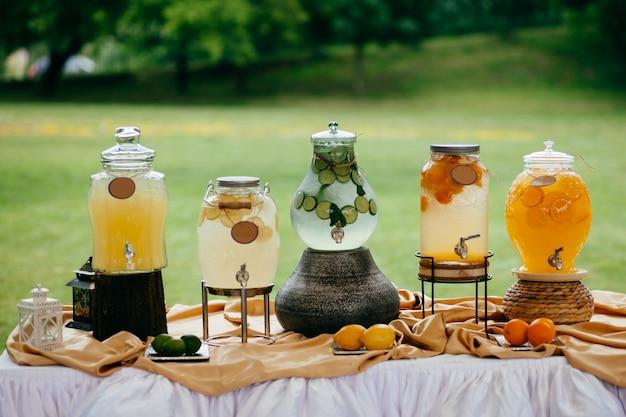 Boisson fraîche dans des pots de citrons, citron vert et oranges sur une table de fête blanche Photo Premium
