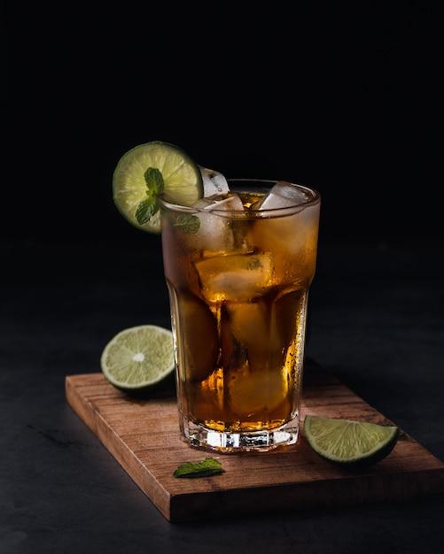 Boisson gazeuse rafraîchissante avec des tranches de citron vert dans une tasse en verre sur fond noir Photo gratuit
