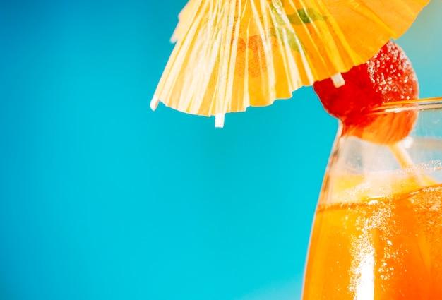 Boisson orange à la fraise dans un parapluie en verre décoré Photo gratuit