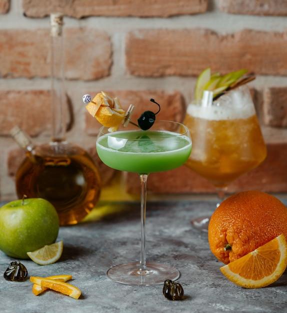 Boisson à la pomme verte garnie de zeste d'orange dans un verre à longue tige Photo gratuit