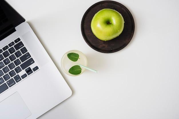 Boisson rafraîchissante avec des pommes et un ordinateur portable Photo gratuit