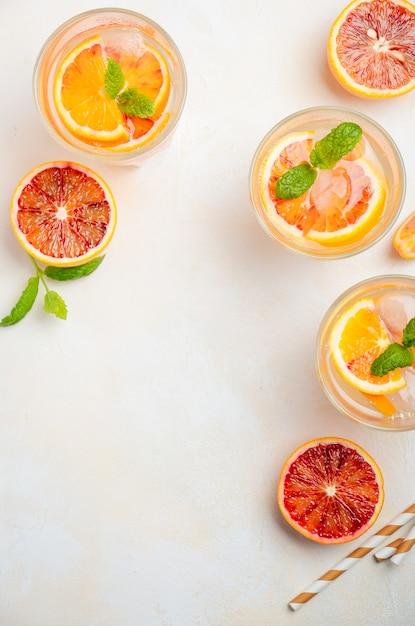 Boisson rafraîchissante avec des tranches d'orange sanguine dans un verre sur un fond de béton blanc Photo Premium