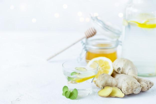 Une boisson saine au gingembre dans une tasse. racine de gingembre, miel dans un bocal, citron sur une table blanche. Photo Premium