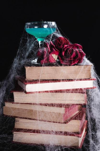 Boisson verte avec des roses, des livres et une toile d'araignée Photo gratuit
