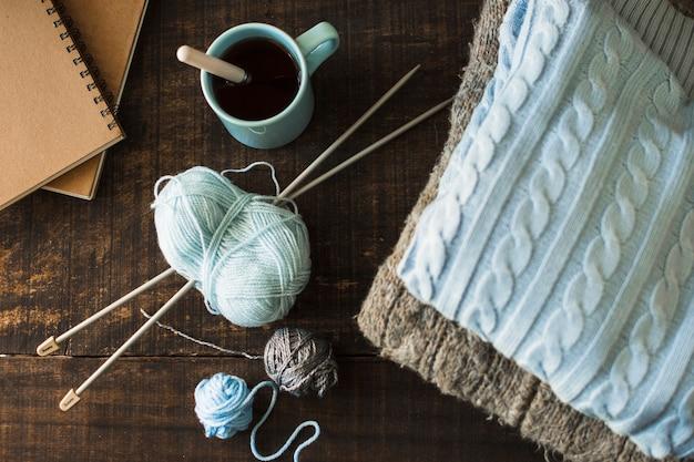 Boissons et cahiers près des fournitures de tricot et des vêtements chauds Photo gratuit