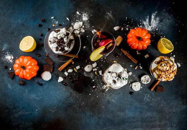 Boissons chaudes d'automne-hiver, chocolat chaud, latte de citrouille, latte au café au caramel et aux arachides, vin chaud, fond sombre confortable Photo Premium