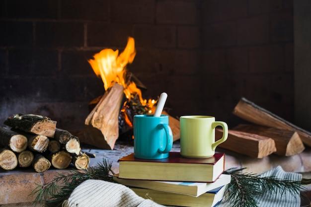 Boissons et livres près de la cheminée Photo gratuit