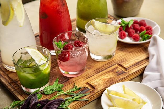 Boissons non alcoolisées estivales, un ensemble de limonades. des limonades dans des pichets sur la table, autour desquelles sont disposés les ingrédients. Photo Premium
