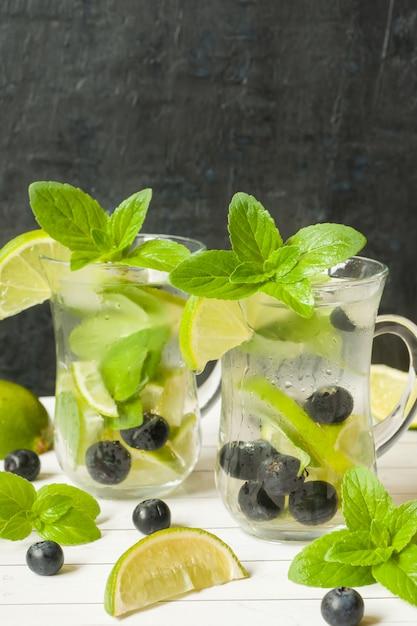 Boissons rafraîchissantes d'été limonade ou cocktail mojito à la glace au citron vert et aux bleuets. Photo Premium
