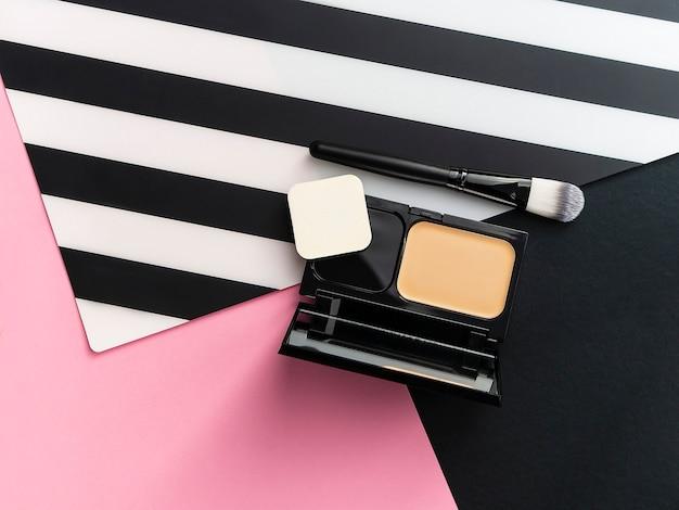Boîte avec base solide et miroir, applicateur de maquillage sur fond rayé rose, blanc et noir. Photo Premium