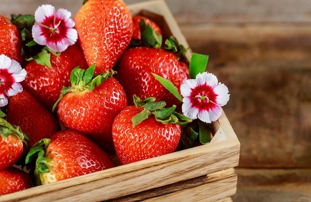 Boîte en bois de fraises rouges mûres fraîches sur un marché de producteurs Photo Premium