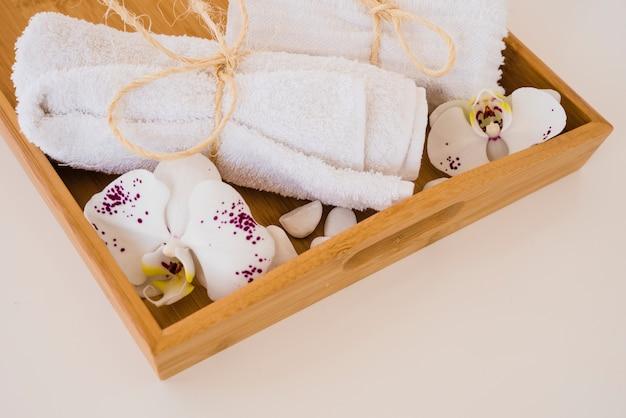 Boîte en bois avec des serviettes et des fleurs Photo gratuit