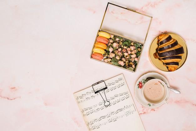Boîte avec des boutons de fleurs et des biscuits près de la tasse à café sur la table Photo gratuit