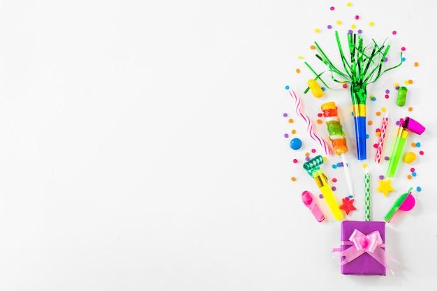 Boite cadeau; bonbons et accessoires de fête sur fond blanc Photo gratuit