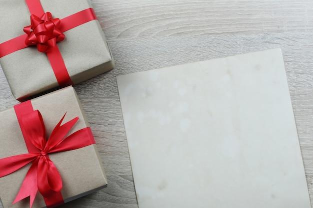 Boîte cadeau brune et papier vintage sur plancher en bois. Photo Premium
