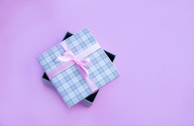 Boîte Cadeau à Carreaux Gris Avec Noeud Rose Sur Fond Rose Image Avec Espace Copie Photo Premium