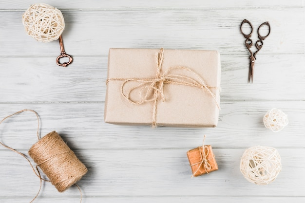 Boite cadeau; ciseaux à bobines et boules décoratives sur un bureau en bois blanc Photo gratuit