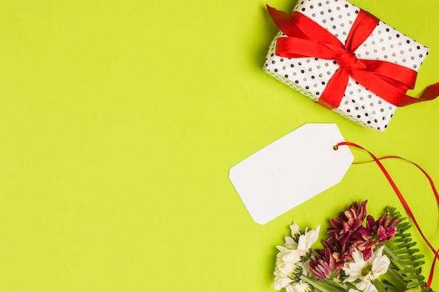 Boîte cadeau emballé à pois avec étiquette vierge et bouquet de fleurs sur fond vert Photo gratuit