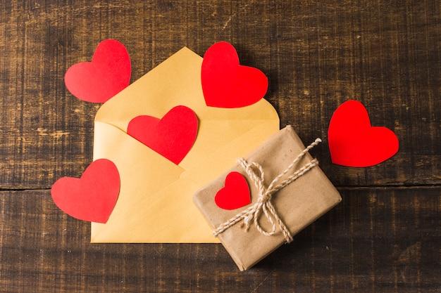 Boîte-cadeau et enveloppe avec des coeurs rouges sur le bureau Photo gratuit