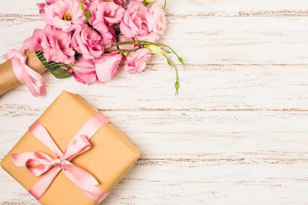 Boîte de cadeau et de fleur d'eustoma rose enveloppé sur une vieille table blanche Photo gratuit