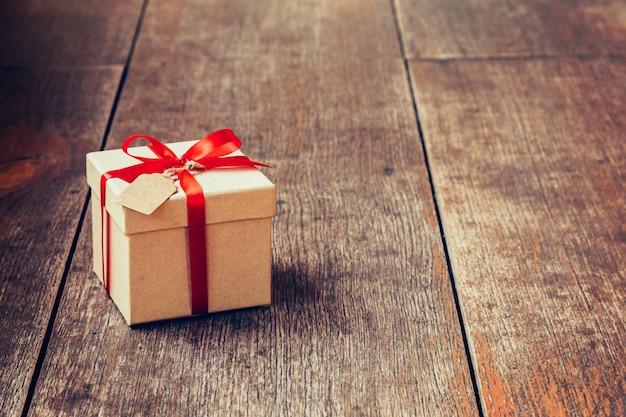 Boîte cadeau marron et ruban rouge avec étiquette sur fond en bois avec de l'espace. Photo Premium