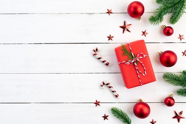 Boîte de cadeau de noël boules rouges avec des branches d'épinette, pommes de pin, baies rouges sur backg en bois Photo Premium
