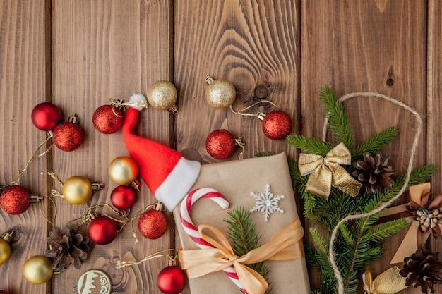 Boîte de cadeau de noël, décor de nourriture et branche de sapin sur une table en bois. vue de dessus avec fond Photo Premium