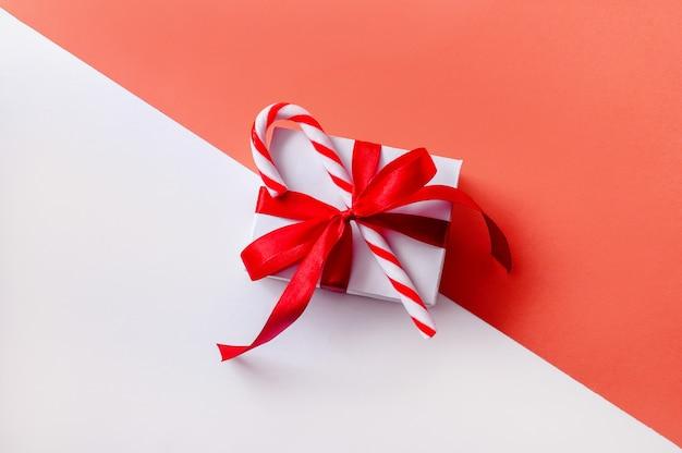 Boîte-cadeau De Noël Sur Espace Rose Et Blanc Avec Des Bonbons. Composition Minimale Créative. Photo Premium