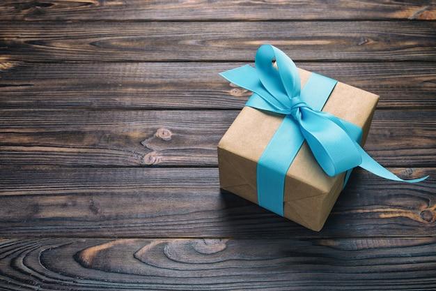 Boîte-cadeau en papier avec ruban bleu sur bois foncé Photo Premium