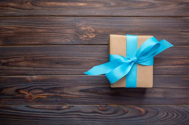 Boîte-cadeau en papier avec ruban bleu sur un cadeau de noël en bois foncé, vue de dessus avec espace de copie Photo Premium