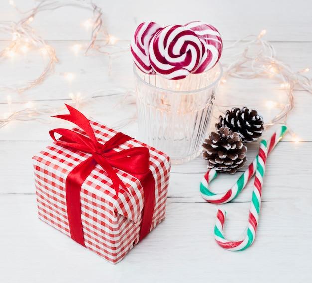 Boîte cadeau près de verre avec sucettes, cannes de bonbon et guirlandes Photo gratuit