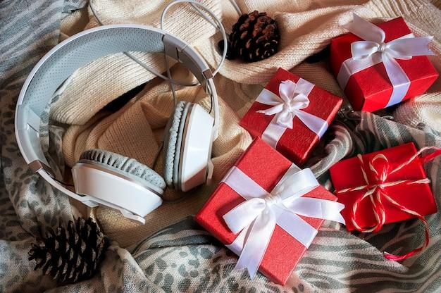 Boîte-cadeau avec ruban blanc, casque et écharpe sur un chandail blanc. sur la lumière Photo Premium