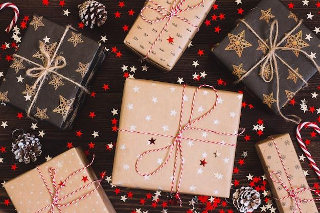 Boîte de cadeau de vacances de noël sur la table de fête décorée avec des pommes de pin et des étoiles scintillantes Photo gratuit