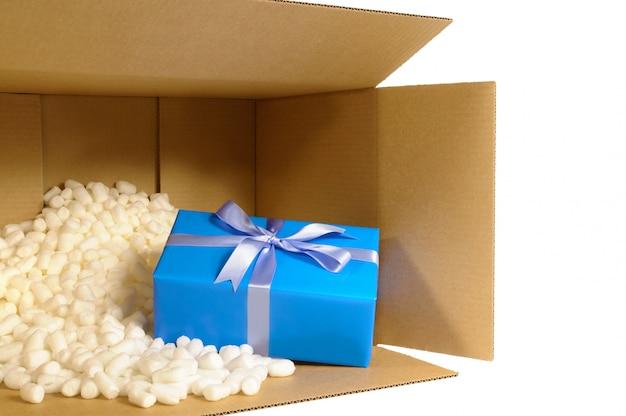 Boîte en carton avec cadeau bleu et pièces d'emballage en polystyrène. Photo Premium