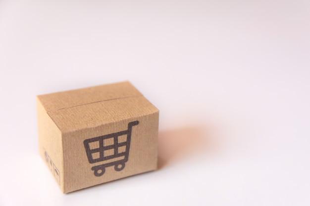 Boîte en carton ou colis avec logo chariot de supermarché sur fond blanc. avec espace de copie Photo Premium
