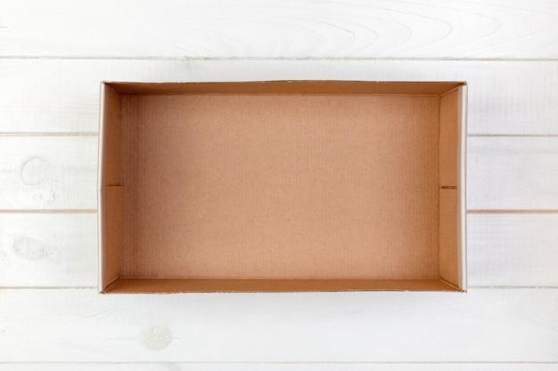 Boîte de carton vide sur une vue de dessus de fond en bois blanc Photo Premium