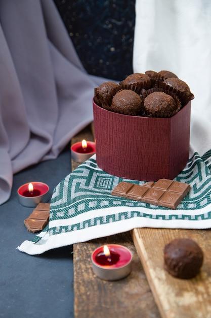Boîte de chocolat et bougies enflammées sur le bois Photo gratuit