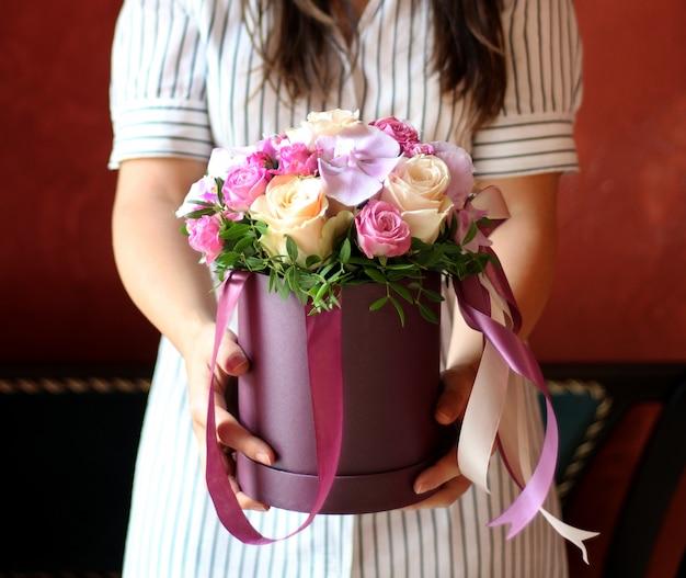 Boîte de fleurs avec ruban dans les mains de la fille Photo Premium