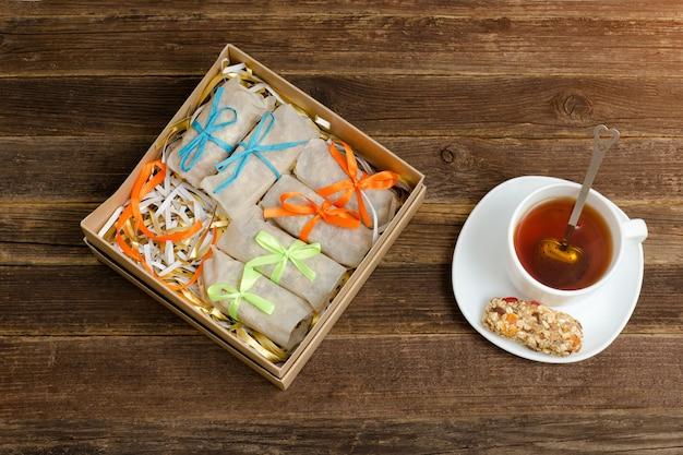 Boîte à friandises. un bar de muesli et une tasse de thé. vue de dessus Photo Premium