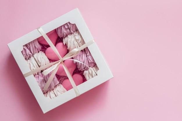 Boîte à guimauves et macarons sur fond rose Photo Premium