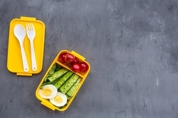 Boîte à lunch avec des aliments sains sur fond gris Photo Premium
